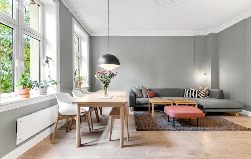Leiligheten har en lys og fin stue med delikate farger. Store vinduer gir rikelig med lysinnslipp.
