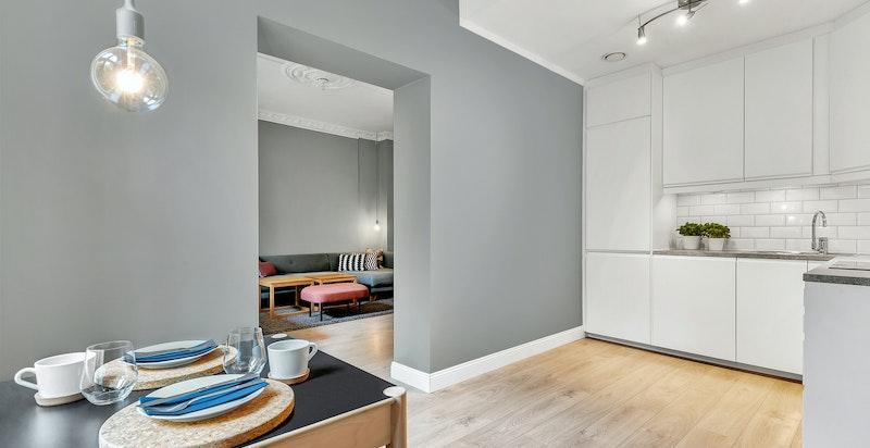 Kjøkkenet har integrerte hvitevarer, malte glatte fronter og belysning under overskap.