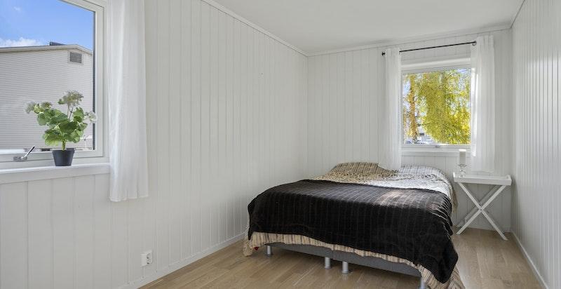 Leiligheten består av romslig soverom med plass til dobbeltseng og tilhørende nattbord.