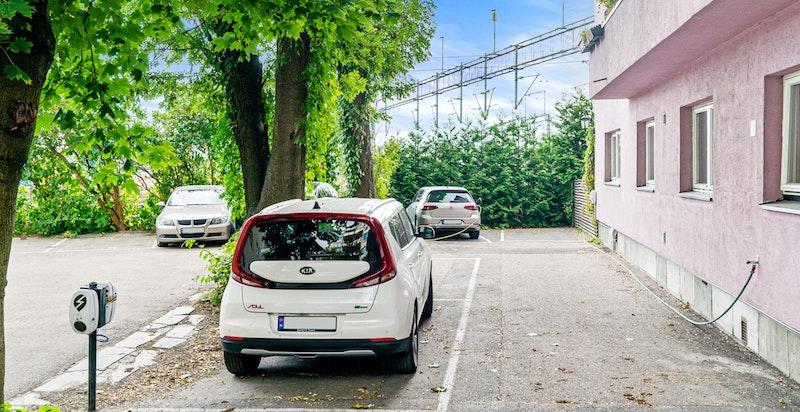 P-plass med elbil-lader rett utenfor bygget