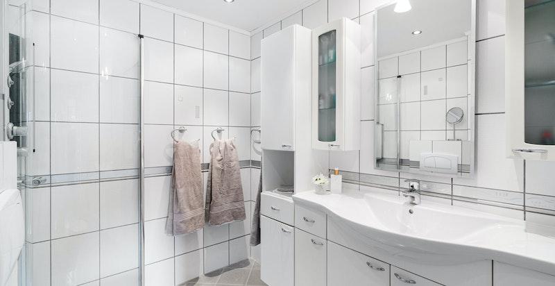 Pent bad som er innredet med dusjhjørne med innfellbare glassdører, toalett, servantskap og speil