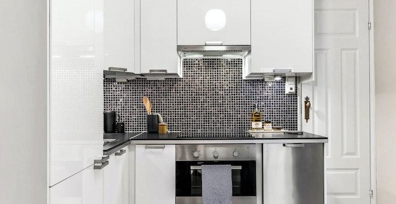 Kjøkkenet har en tiltalende og moderne kjøkkeninnredning med hvite høyglansfronter i kombinasjon med en skapdør i frostet glass, samt laminat benkeplate.