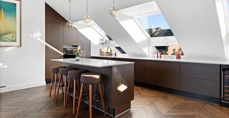 HTH kjøkkeninnredning med mørke eikefinerte fronter og benkeplate i lys kompositt.