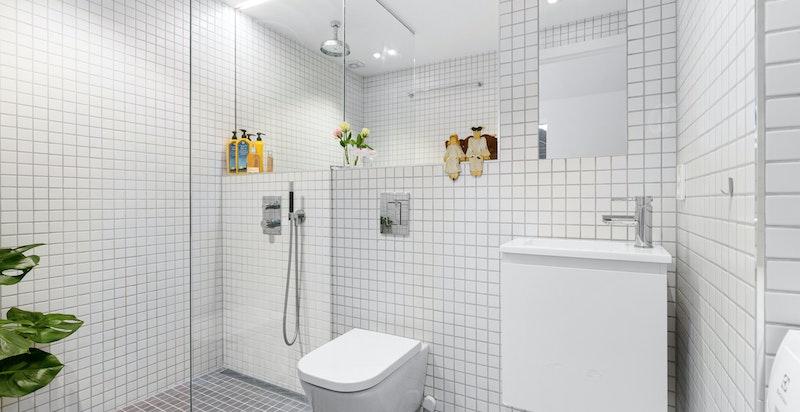 Flislagt romslig baderom tilknyttet entré, rommet er innredet med vegghengt klosett, dusj og innredning med servant.