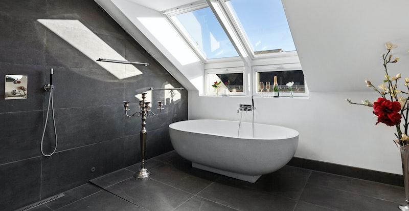Hovedbaderom innredet med frittstående badekar, åpen dusj og servant.