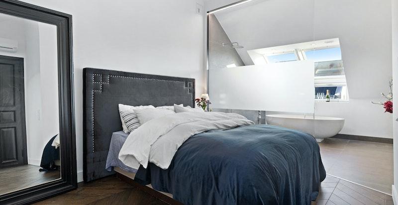 Glassvegg med dør mellom, soverom og bad, samt separat toalett med tett dør.