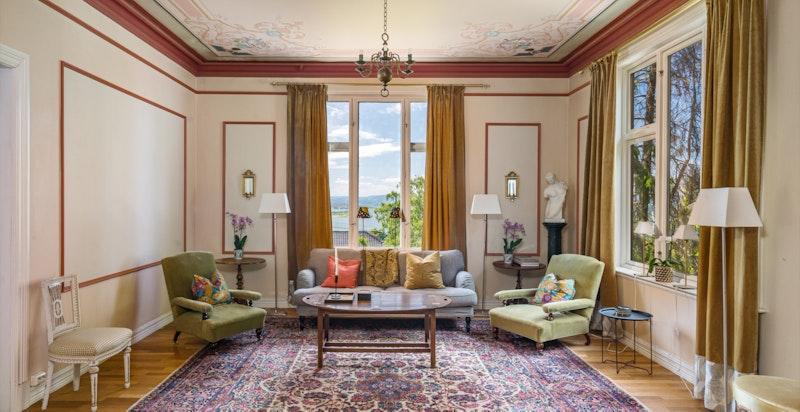 Stor stue med klassiske detaljer og store vindusflater