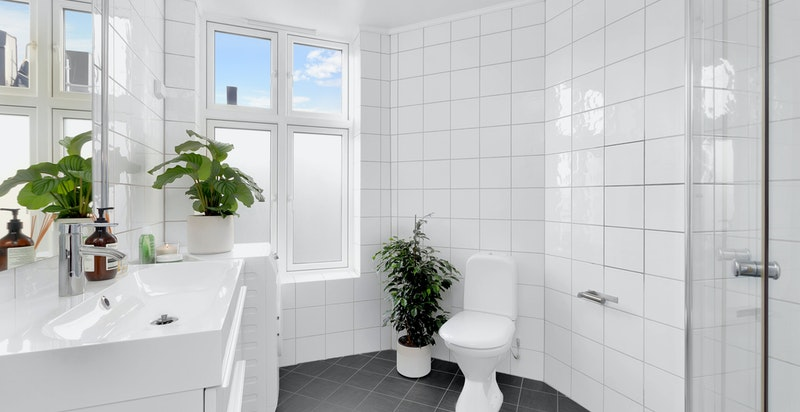 Badet har tidløse farger på fliser og moderne baderomsinnredning