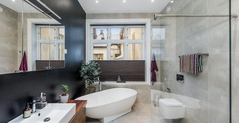 Bad 1 med frittstående badekar, dusjnisje på fliser, servant på trebenk og hyller