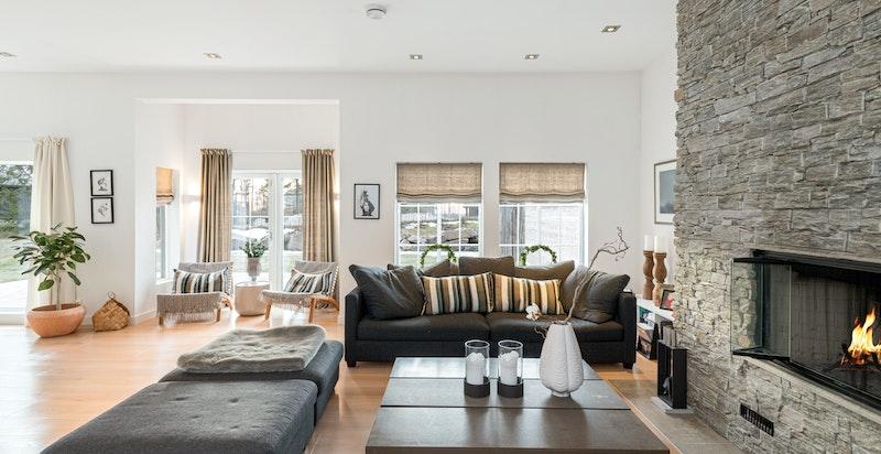 Herlig stue med flott peis, sjenerøs takhøyde, utgang til hage og tilknytning til spisestue og kjøkken innenfor