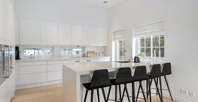 Moderne og romslig kjøkken med barløsning i dels åpen løsning mot spisestue
