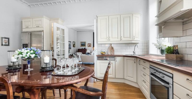 Heltre benkeplater med nedfelt oppvaskkum og fliser på vegg mellom oppvaskbenk og overskap