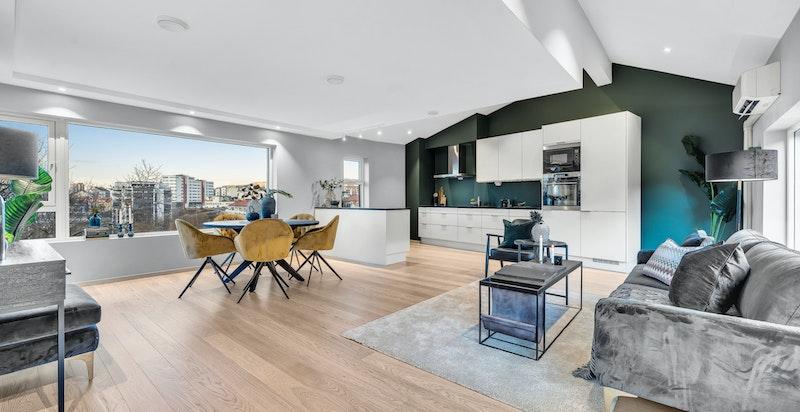 Det åpne rommet som huser kjøkken, stue og spisestue har store vinduer for maksimalt gjennomlys