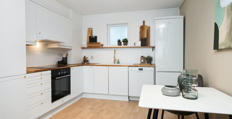 Kjøkkeninnredning med integrerte hvitevarer og sitteplass