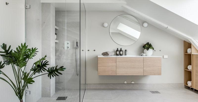Baderommet er innredet med glassvegger til dusjen
