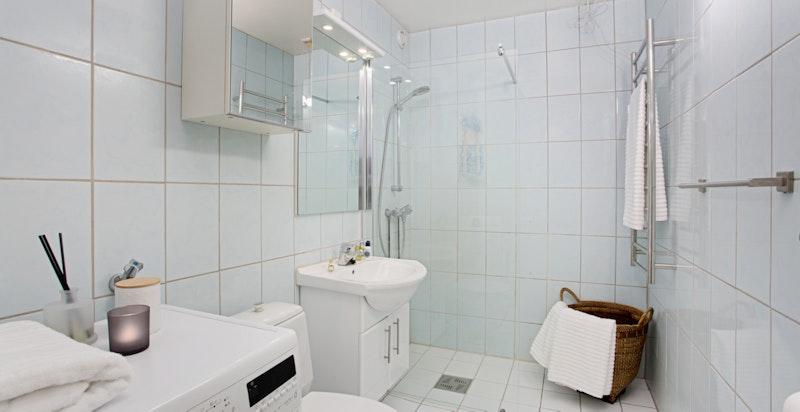 Romslig bad som er innredet med dusj, servantskap, speilskap og toalett
