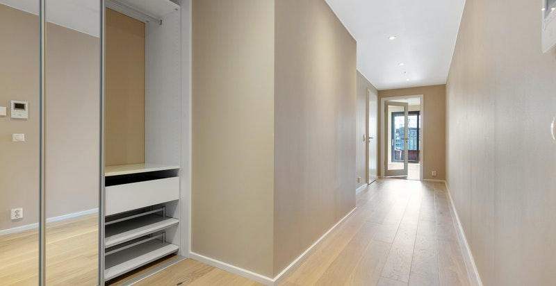 Entreen gir et godt førsteinntrykk av boligen med downlightsbelysning og plassbygget garderobeinnredning.