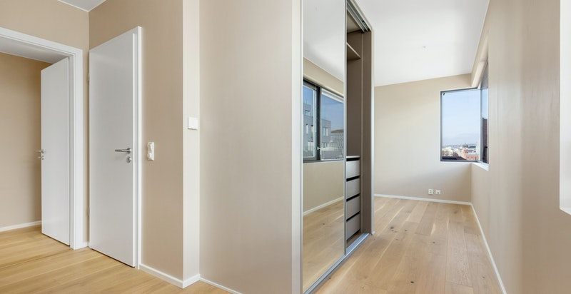 Stort hovedsoverom med eget bad, plassbygget garderobeskap og walk-in-closet/bod.