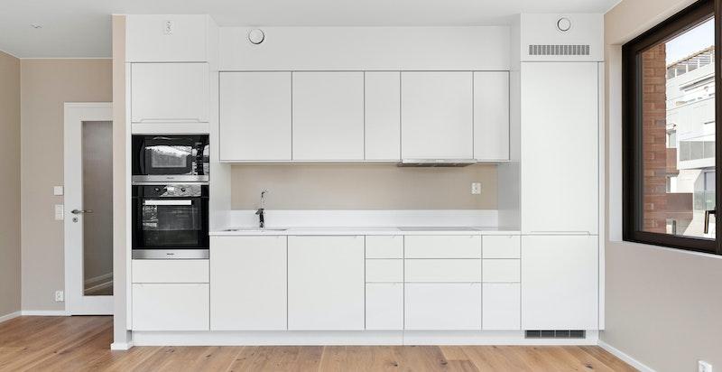 Modellen heter Avantgarde og består av benkeskap, overskap og høyskap. Benkeplate i hvit Corian.