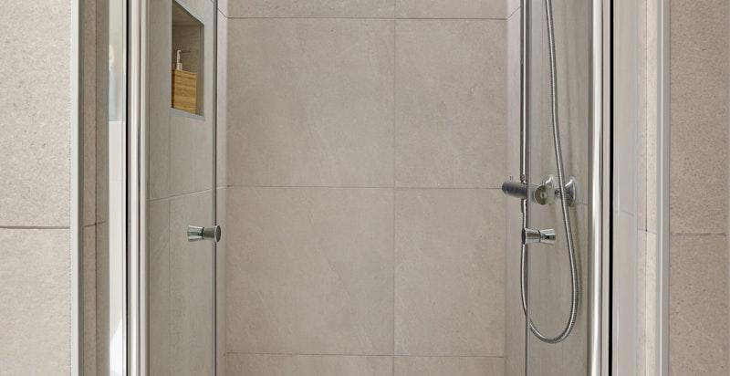 Badet har en romslig dusjnisje med lekre detaljer som designbelysning i himling og flotte fliser levert av Modena