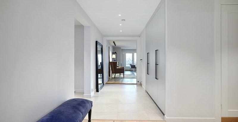 Romslig og lys entré/hall med snekkerbygde garderobeskap