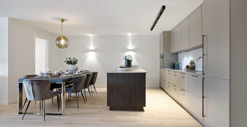 Kjøkkenet er tilbaketrukket fra stuen, men fremdeles i en åpen, smart og sosial løsning med spiseplass tilknyttet