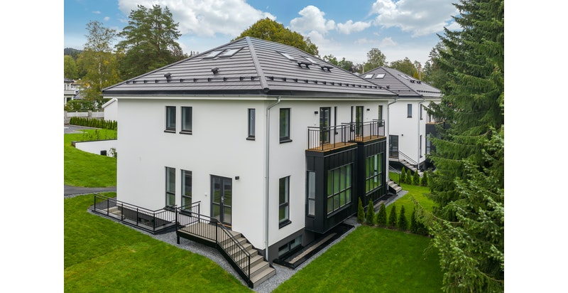Huset er tilnærmet vedlikeholdsfritt med pusset fasade i hvit utførelse og elementer av sort blikk på utkragede bygningsdeler fra soverom i 2 etasje og ut fra stue i 1 etg. Øvrige detaljer i sort blikk og galvanisert stål