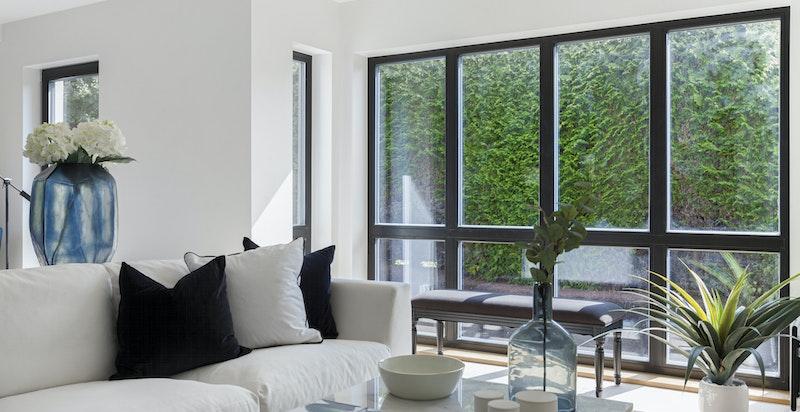 Sorte energiglassvinduer mot hyggelig hage