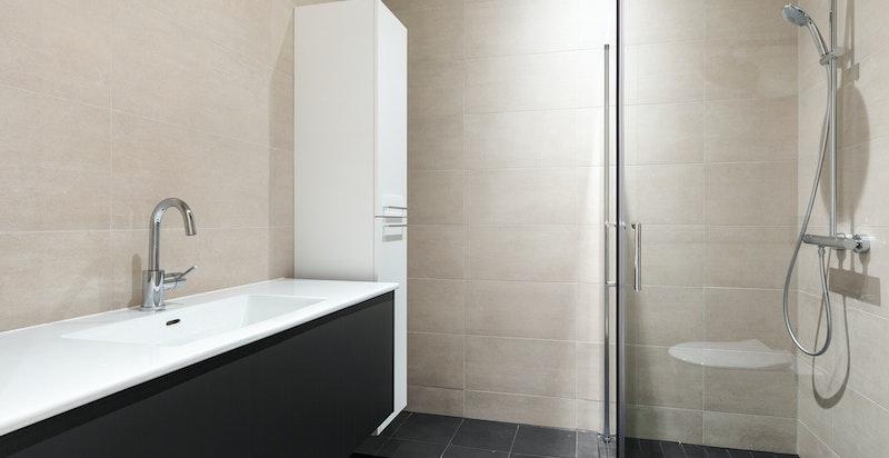 Lekkert bad med dusj og badekar i grunnplan