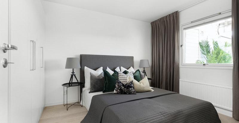Romslig soverom med god plass til dobbeltseng og nattbord på hver side. Innredet med rikelig garderobeinnredning.