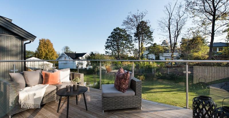Romslig terrasse med utgang fra stue/spisestue. Trapp som fører til hage og terrasseplatting