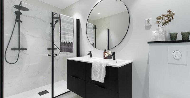 Det lekre badet tilhørende hovedsoverom er innredet med dobbelt servantskap, dobbel regnfallsdusj med dusjdører, samt vegghengt toalett