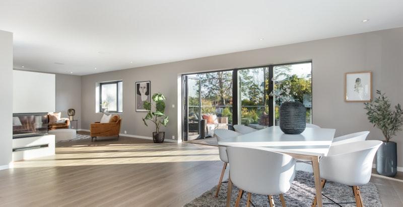 Stor og åpen stue/spisestue med utgang til en solrik terrasse
