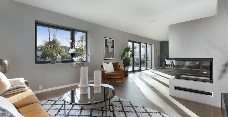 Stue/spisestue har moderne peisovn med hev/senk dør og glass på 3 sider