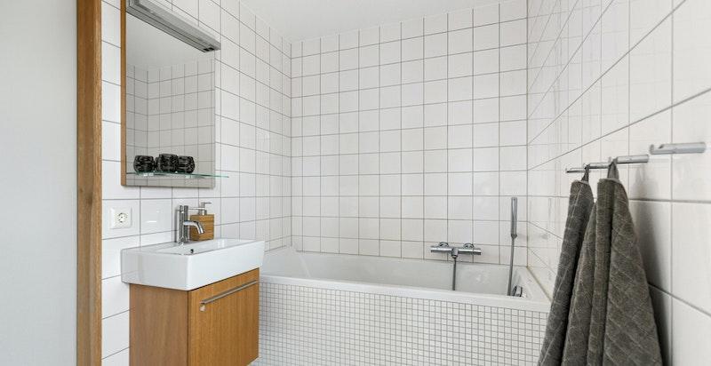Bad tilknyttet hovedsoverom, innredet med dusjbadekar, servant og vegghengt toalett.