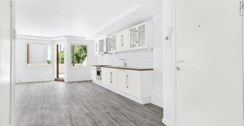 Ved siden av kjøkkeninnredning er det nisje til kjøleskap.