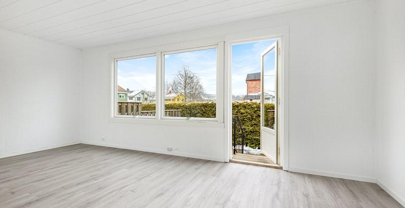 Stuen får rikelig med naturlig lys fra store vindusflater. Det er lagt nytt laminatgulv i hele 1. etasje og nymalte flater.