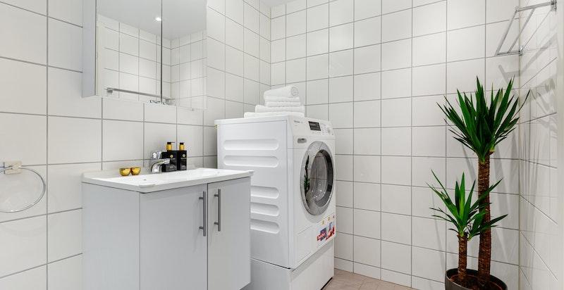Romslig moderne bad med dusjhjørne og opplegg for vaskemaskin/tørketrommel