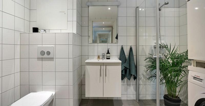 Baderom 2 er helfliset og utstyrt med veggmontert toalett, dusjhjørne, servantinnredning og speil med overlys