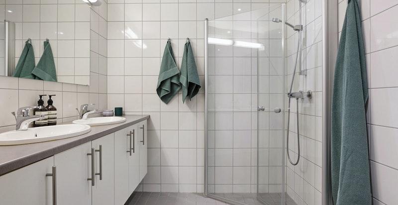 Hovedbad utstyrt med veggmontert toalett, dusjhjørne, servantinnredning m/2 servanter og speil med overlys.