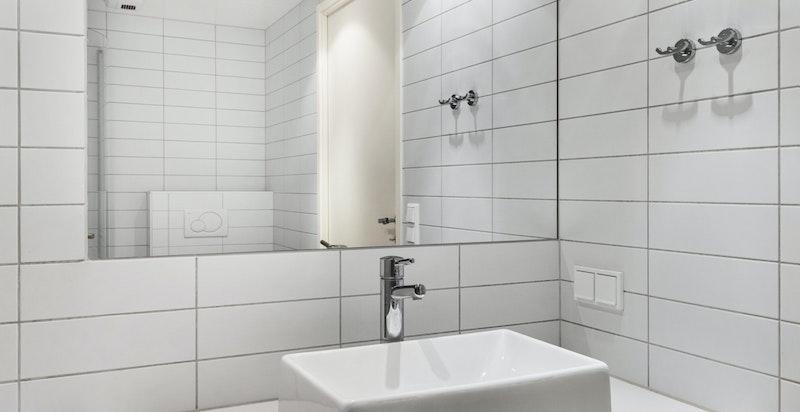 Veggmontert baderomsinnredning med oppbevaringsplass til baderomsartikler og servant i underskap med ett greps blandebatteri og speil over servant.