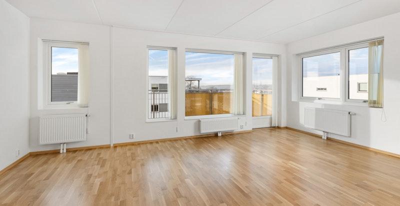 Innvendig fremstår leiligheten som luftig med store vindusflater som gir rikelig med naturlig lys.