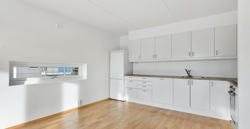Kjøkkeninnredning med hvite glatte fronter og laminat benkeplate.