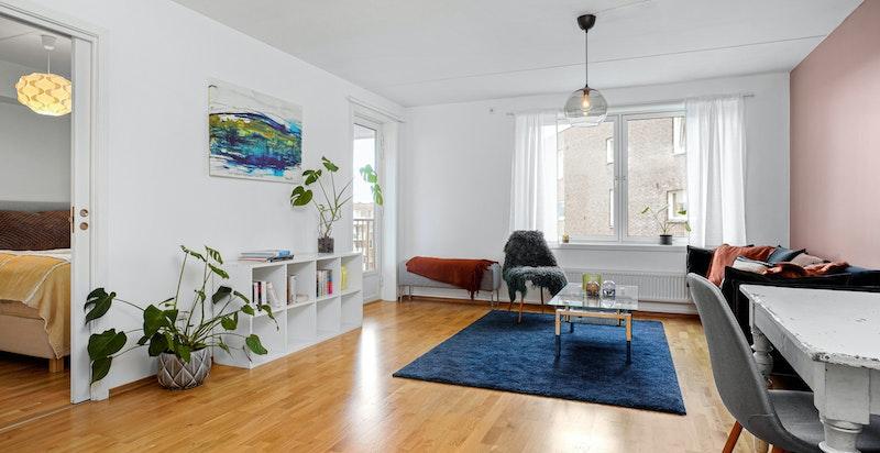 Lys stue med plass til spisebord og sofaseksjon. Utgang til balkong.