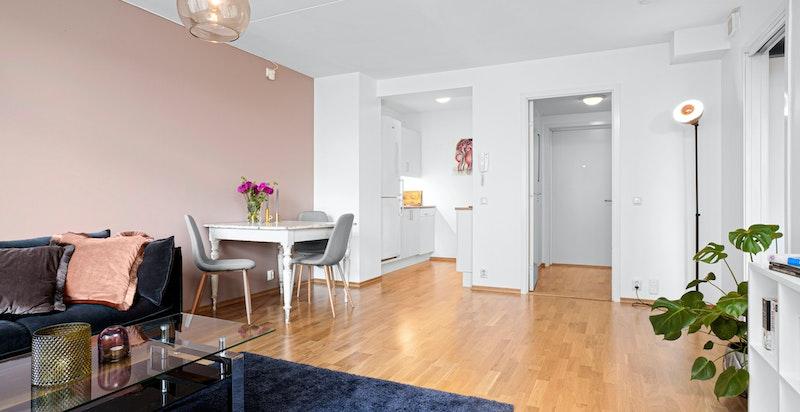 Lys stue med plass til spisebord og sofaseksjon.