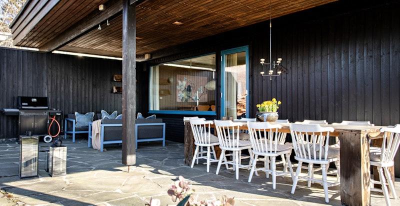 Terrassen ut fra stue er overbygget og lun til langt utpå høsten. Her står terrassemøblene under tak, skjermet for vær og klare til bruk