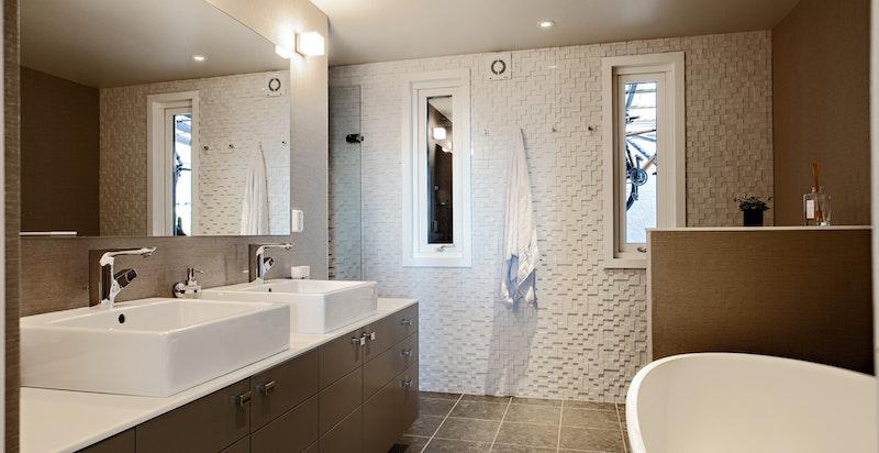Lekkert og stilrent bad med dobbelservant, badekar og dusjnisje. Eksklusive fliser, våtromstapet og integrert belysning