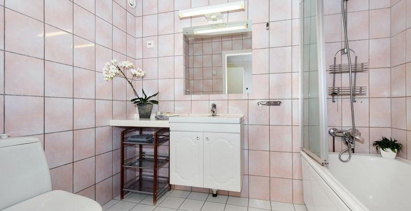Eldre men praktisk baderom med badekar, servant og toalett.