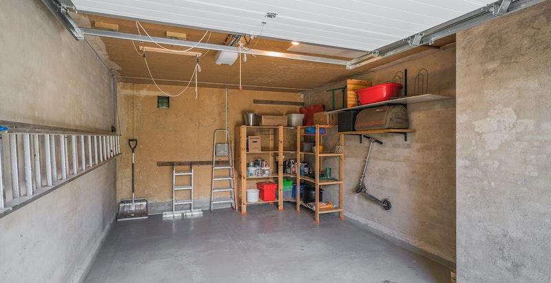 Garasje med god plass for en bil og lagring.