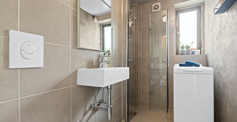 Delikat og innbydende baderom med dusjhjørne med termostatbatteri og dusjvegger i herdet glass, veggmontert toalett, helstøpt servant og opplegg til vaskemaskin